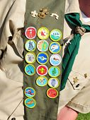stock photo of boy scout  - Boy scout wearing his bandoleer with 17 merit badges - JPG