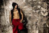 foto of thug  - Muscular thug leaning against dirty grungy wall looking to a side at large copyspace - JPG