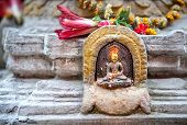 picture of pooja  - Buddha statue with yellow color tikka in Patan Nepal - JPG