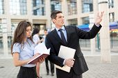 pic of secretary  - Young businessman and his secretary standing in front of office building - JPG