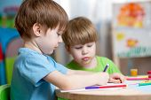 stock photo of nursery school child  - children boys painting in nursery at home - JPG