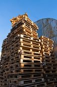 image of wooden pallet  - Stacked up colorful wooden cargo pallets against a blue sky - JPG