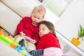 stock photo of toy phone  - Two children playing on the carpet - JPG