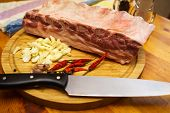 stock photo of ribs  - Fresh pork ribs meat marinated and prepared for roast with garlic. Laying on a wooden table on a round cutting board with knife chilly peppers and garlic. ** Note: Shallow depth of field - JPG
