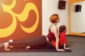foto of om  - Mother and child yoga practice on the background of the Indian symbol of OM - JPG