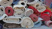stock photo of piles  - Pile of carpets and rugs in rolls - JPG