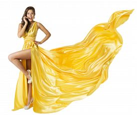 stock photo of flutter  - Woman Beauty Fashion Dress Beautiful Girl In Flying Yellow Fluttering Gown Standing on One Leg High Heels Surprised with Open Mouth - JPG