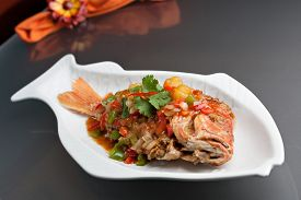 picture of red snapper  - Freshly prepared Thai style whole fish red snapper dinner with tamarind sauce on a white fish shaped plate. Shallow depth of field. ** Note: Shallow depth of field - JPG