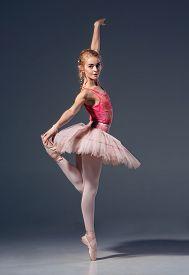 stock photo of ballerina  - Portrait of the ballerina in ballet pose on a grey background - JPG