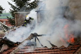 stock photo of firefighter  - Firefighters are extinguishing fire on a burning house roof - JPG