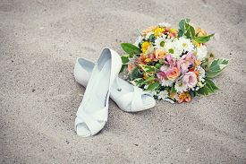 picture of sand lilies  - Bridal shoes and wedding bouquet on the sand - JPG