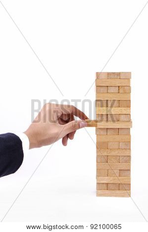 Businessman Hand Playing With The Wood Game (jenga).