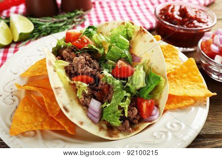Mexican food Taco in plate on wooden table, closeup