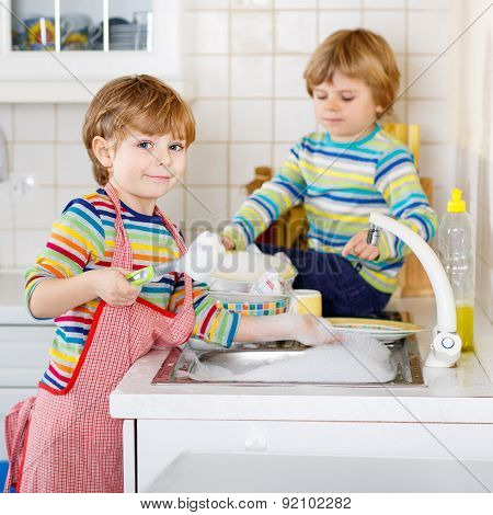 Two Funny Little Boy Friends Washing Dishes In Domestic Kitchen