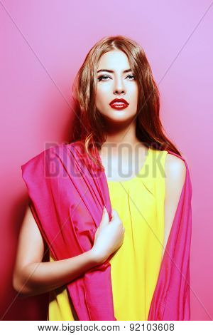 Beauty portrait of a sensual young woman in bright crimson headscarf over pink background. Beauty, fashion. Cosmetics.