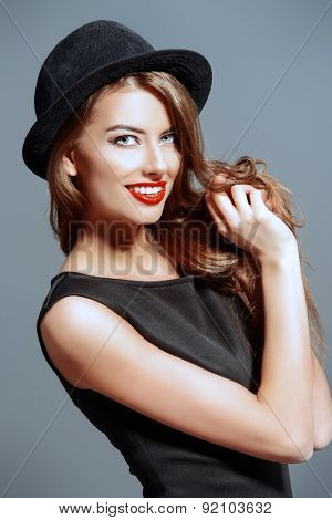 Joyful pretty girl wearing black dress and black classic hat smiling at camera. Beauty, fashion concept. Hipster style.