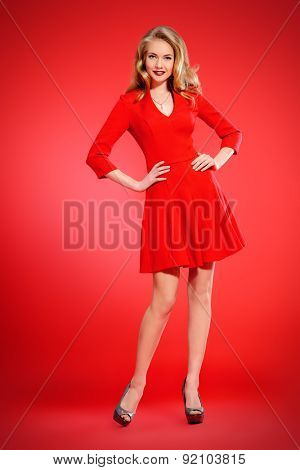 Full length portrait of a charming young woman in red dress and with blonde curled hair. Beauty, fashion. Cosmetics, make-up. Red background.
