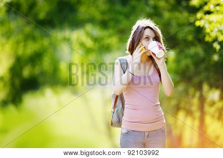 Woman with smartphone and coffee in summer day park.