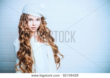 Cute teenager girl with beautiful long curly hair wears white knitted jersey and beret. Beauty, fashion.