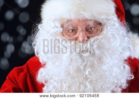 Close-up portrait of Santa Claus over black background. Christmas time.
