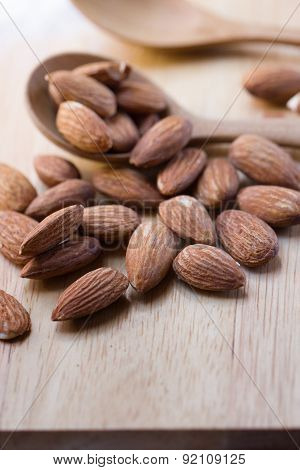 Almonds In Spoon On Brown Wooden Background