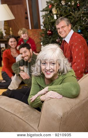 Senior Woman With Family By Christmas Tree