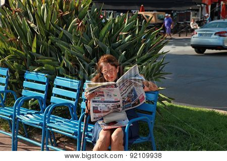Cannes, France -  July 5, 2014. Woman Reading A Newspaper On The Boulevard De La Croisette. Cannes L