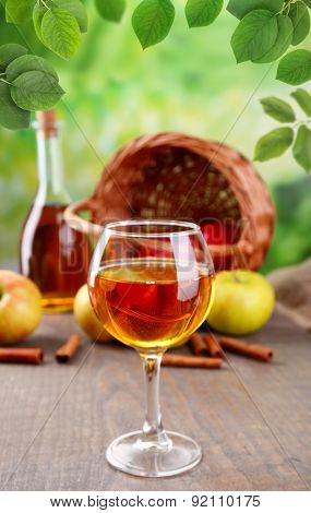 Apple cider in glass with cinnamon sticks and fresh apples on wooden table on natural background