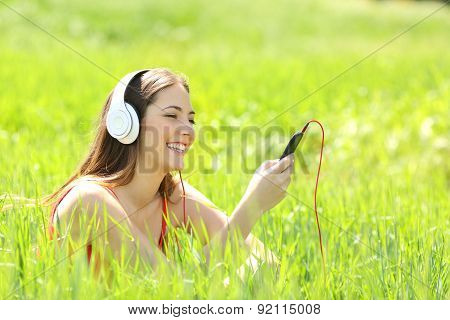 Girl Listening Music With Headphones And Smart Phone In A Field
