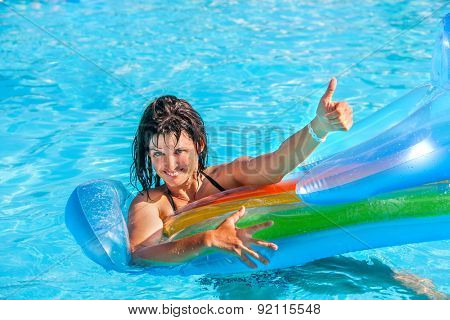 Happy woman  swimming on inflatable beach mattress and showing thumb up.