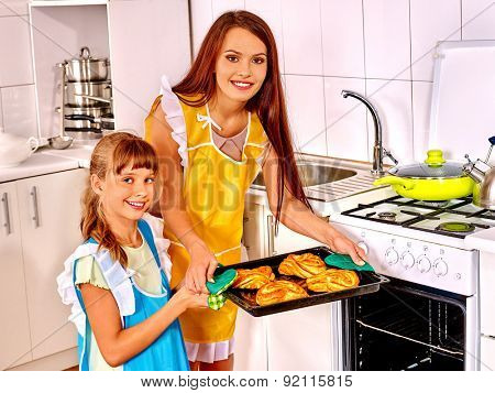 Mother and daughter bake cookies at home kitchen.