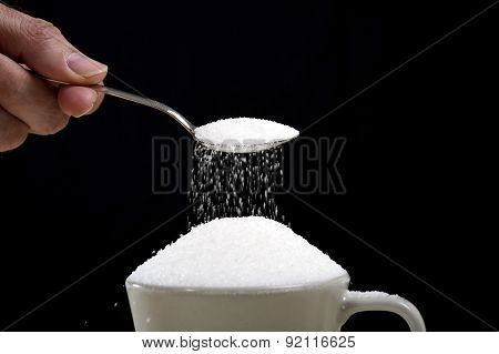 Man Hand With Spoon Pouring A Crazy Lot In Full Coffee Cup In Addiction Concept