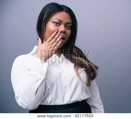 African businesswoman covering her mouth over gray background. Looking at camera