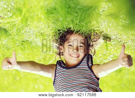 Portraits of happy kid playing upside down outdoors in summer park with thumbs up