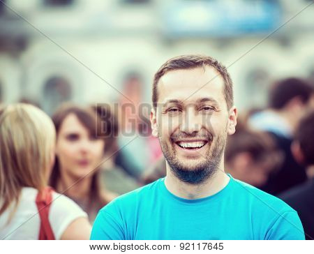 Smiling man standing on a crowded street