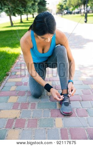 Young sports woman tying her shoelace outdoors