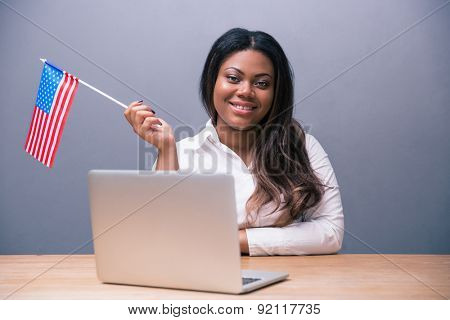 Happy african businesswoman sitting at the table with laptop and US flag over gray background. Looking at camera