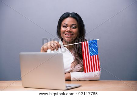 Smiling african businesswoman sitting at the table with laptop and US flag over gray background. Looking at camera