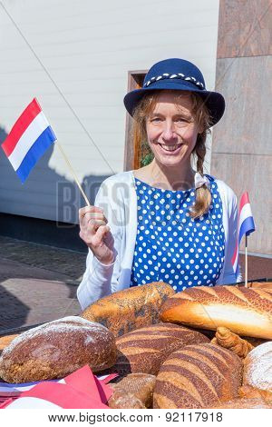 European woman with breads waving with dutch flag