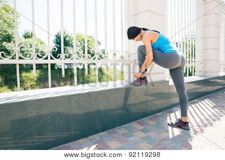 Sporty woman runner tying shoelaces outdoors