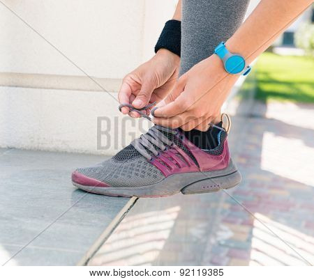 Closeup image of a female hands tying shoelaces outdoors