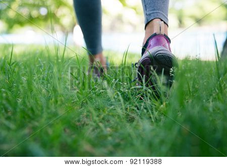 Closeup image of a sports footwear on female feet running on green grass