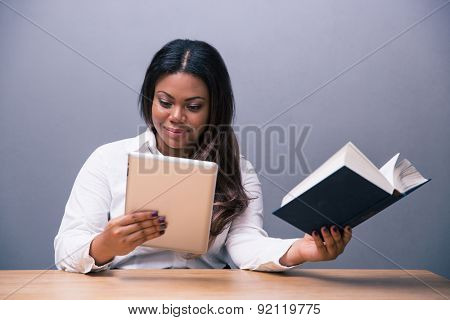 African businesswoman choosing between e-book or paper book over gray background. Looking at camera