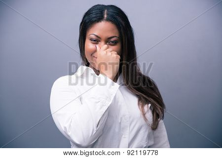 African businesswoman covering her nose over gray background and looking at camera
