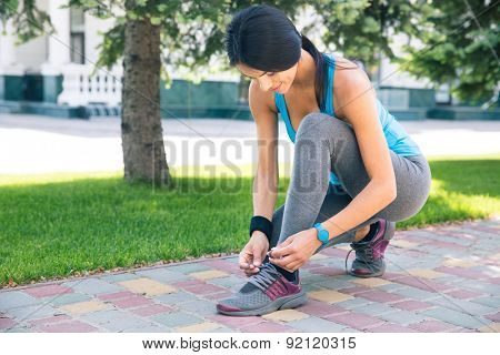 Fitness sporty woman tying her shoelace outdoors