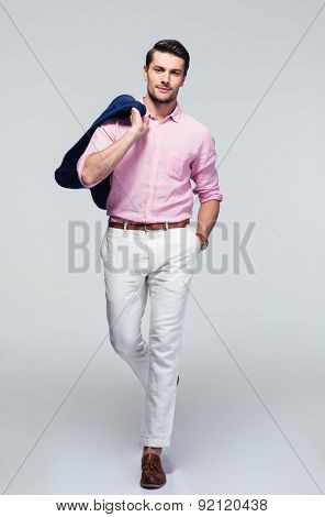 Full length portrait of a handsome fashion businessman with jacket on shoulder over gray background. Looking at camera