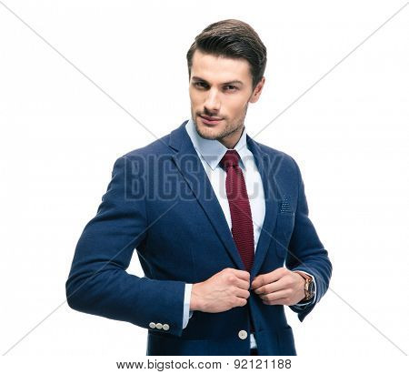Confident businessman putting on suit jacket isolated on a white background. Looking at camera