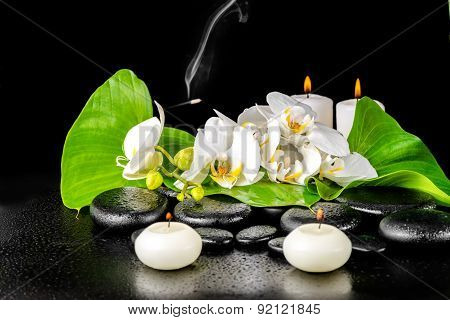 Spa Concept Of Orchid Flower, Phalaenopsis, Leaf With Dew, Candles, Smoke On Black Zen Stones, Close