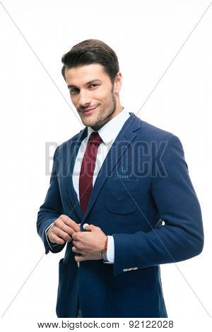 Happy handsome businessman putting on suit jacket isolated on a white background. Looking at camera