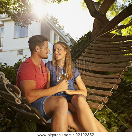 Romantic Couple Relaxing On Hammock Drinking Wine